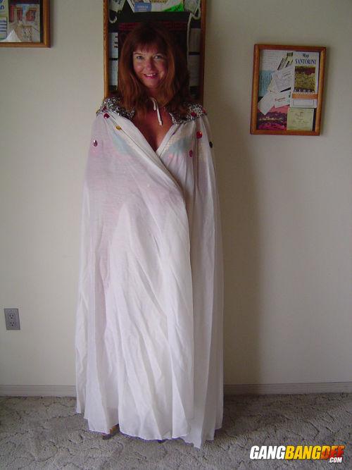 Hot mature Dee Delmar doffs her skimpy carnival costume to toy her twat