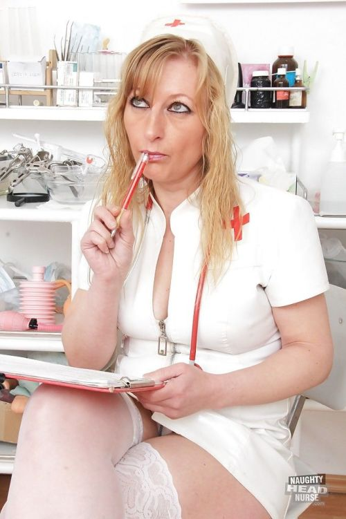 Mature in nurse uniform is lying in the chair with spread legs