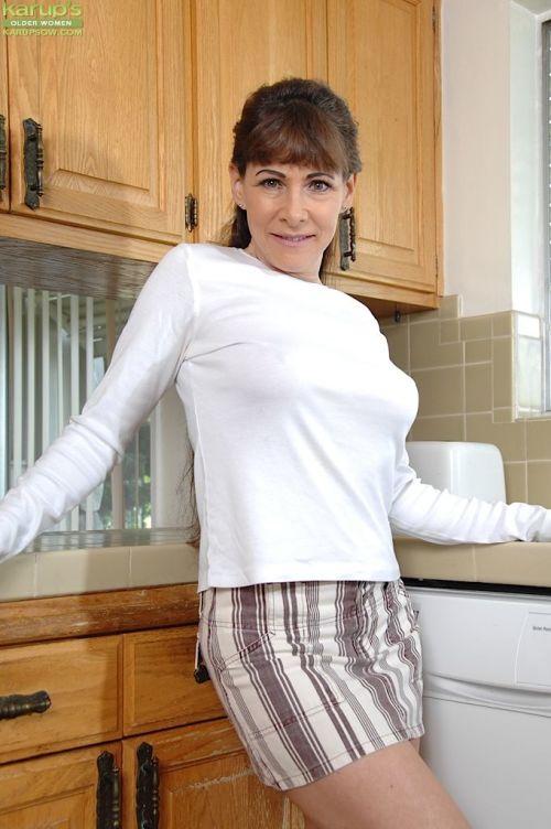 Busty aged lady Alexandra Silk slipping undies over pierced cunt in kitchen